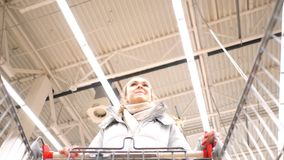 Low angle shot girl comes up to cart and leaves trolley. Low angle shot pretty girl comes up to shopping cart and leaves trolley against high ceiling in stock footage