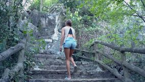 Low angle shot girl in shorts goes up stone steps on hill. Back low angle shot tired girl in denim shorts goes up stone steps with wooden handrail on hill stock video footage