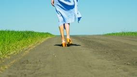 Low-angle shot girl slim legs in skirt walk along road. Backside low-angle shot girl slim legs in flowing skirt walk along ground road near green fields against stock video