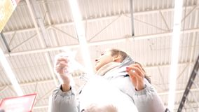 Low angle shot girl ties plastic bag puts into cart. Low angle shot pretty girl ties plastic bag with products puts into shopping cart against high ceiling in stock video
