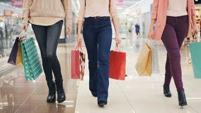 Low angle shot of group of young women walking in shopping mall with colorful gift bags in hands. Slender girls are stock video