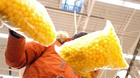 Low angle shot guy holds large yellow corn ball packages. Low angle shot handsome guy in red jacket holds large packages with sweet corn balls in supermarket stock video