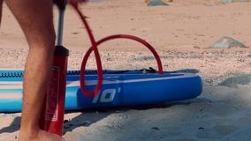 Low-angle shot guy inflates paddle board with pump at leg. Low angle close shot guy inflates blue and white rubber paddleboard with red hand pump on tropical stock video