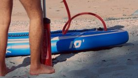 Low-angle shot guy stands in shade pumping paddle board. Low angle close shot guy stands in shade pumping blue and white paddle board with red hand pump on sand stock footage