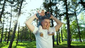 Low angle shot of happy father holding his toddler daughter on shoulders outside stock footage