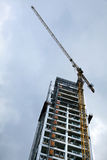 High Rise Construction. Low angle shot of a high rise residential building in the middle of construction, on the background of overcast gray skies Stock Image