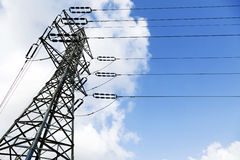 Electricity Pylon. Low angle shot of a high-voltage electricity pylon and power lines, on the background of the blue & white cloudy sky Royalty Free Stock Photography