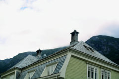 Low Angle Shot of House With Chimney Near Mountain Stock Photos