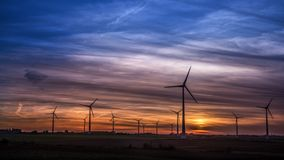 Low angle shot of a lot of windmills in the field under the beautiful sunset sky
