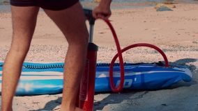 Low-angle shot man inflates paddle board with hand pump. Low-angle close shot man inflates blue rubber paddle board with red hand pump on sand beach on sunny day stock video footage