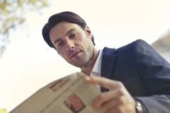 Low Angle Shot of Man Reading Newspaper royalty free stock image