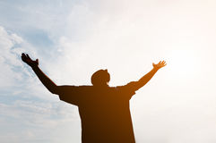 Low Angle Shot of a Man Silhouetted against the Glaring Sun. Low angle shot of a silhouetted man, with arms outstretched in joy, against the glaring light of the Stock Photos