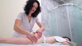 Low angle shot masseur doing anti cellulite massage on buttocks of young woman. Low angle shot of woman masseur doing anti cellulite massage on buttocks of young stock video footage