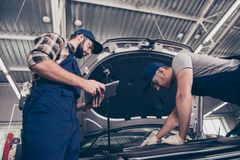 Low angle shot of mechanical engineers experts assistants at work shop in special blue safety outfit uniform, hat head wear with royalty free stock image