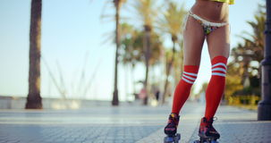 Low Angle Shot of Roller Skating Girl. Riding in Bikini on Tropical Beach Promenade at Sunset. Slow Motion Video Recorded at 120fps stock footage