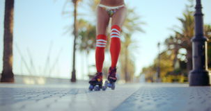 Low Angle Shot of Roller Skating Girl. Riding on Tropical Beach Promenade at Sunset. Slow Motion Video Recorded at 120fps stock video footage