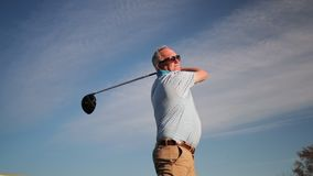 Senior man playing golf. Low angle shot of a senior man swinging a golf club stock footage