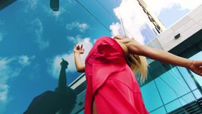 Low angle shot of sensual female dancer performing in red dress outside. Low angle shot of sensual female dancer in red dress performing outside near skyscraper stock video footage