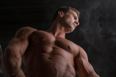 Low angle shot of shirtless male bodybuilder on Stock Photography