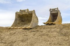 Dredger buckets. Low angle shot showing two old dredger buckets on loamy ground in front of partly blue sky Stock Image