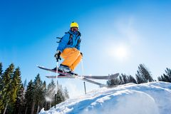 Skier skiing in the mountains. Low angle shot of a skier in colorful gear jumping in the air while skiing on a slope copyspace sunlight extreme adrenaline Stock Images