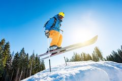 Skier skiing in the mountains. Low angle shot of a skier jumping in the air while skiing in the mountains copyspace. Blue sky, sun and winter forest on the Stock Photos