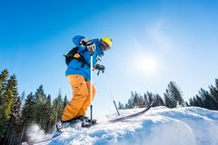 Skier riding in the mountains on a sunny winter day. Low angle shot of a skier riding down the slope at ski resort mountains copyspace seasonal activity sport Stock Image
