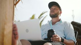 Low angle shot of successful happy relaxed businessman with laptop and drink resting in beach lounge chair on vacation. stock footage