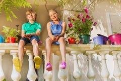 Kids sitting on balustrade among potted flowers royalty free stock image