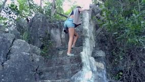 Low angle shot woman in shorts goes up stone stairs. Low angle shot tired young woman in denim shorts goes up stone stairs holding wooden railing stock video footage