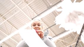 Low angle shot woman takes deploys disposable package. Low angle shot close woman takes disposable package and deploys plastic bag against high ceiling in stock footage