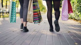 Low angle shot of women`s legs walking in the street with colorful paper bags after busy day in shops. Young people stock video