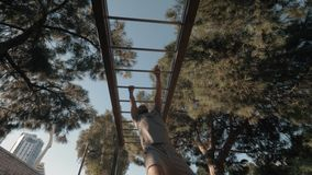 Workout on monkey bar in the park. Low angle shot of a young man having a workout on sports ground in the park. Hand over hand exercise on monkey bar stock video footage