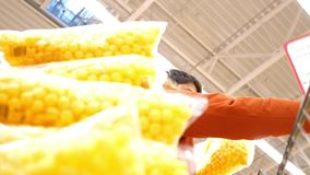 Low angle shot man loads shopping cart with corn ball packs. Low angle shot young man in red jacket loads shopping cart with sweet corn ball packets from stock footage