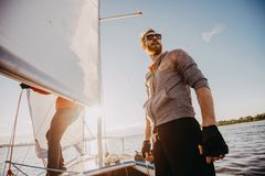 Low angle shot of a young man sailor wearing sunglasses and gloves on a sailing boat at sunset. Image toned in warm. Colors stock images