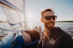 Low angle shot of a young man sailor wearing sunglasses and gloves on a sailing boat at sunset. Image toned in warm. Colors royalty free stock images