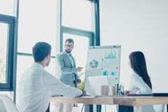 Low angle shot of a young smart brunet bearded manager in spectacles, reporting to the team of colleagues with the flip chart. royalty free stock photography
