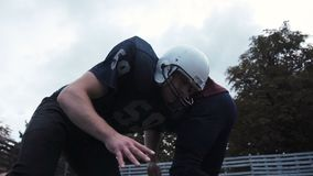 Two American football players hitting each other. Low-angle side view of two American football players hitting each other by accident during match outdoors stock video footage