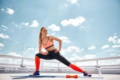 Concentrated lady is having workout on roof royalty free stock image