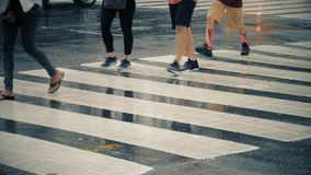 Low Angle Slow Motion Pedestrians on Rainy Manhattan Crosswalk. A slow motion, low angle view of pedestrians crossing a rainy midtown Manhattan street stock footage