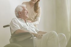 Low angle on smiling and happy disabled elderly man in a wheelch. Low angle on smiling and happy disabled elderly men in a wheelchair and his caregiver in a royalty free stock image