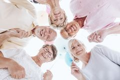 Low angle of smiling seniors. Standing in a circle and celebrating together stock photo