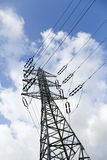 Electricity Pylon. Low angle tilted shot of a high-voltage electricity pylon and power lines, on the background of the blue & white cloudy sky Royalty Free Stock Images