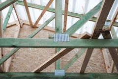 Low angle top close up view photo of wooden roof with metal elements of compounds on reliable partitions and supporting beams. Under white windproof membrane stock photography