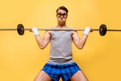 Low angle top view portrait of youngster joke, comic man push ha. Rd weight barbell up on shine yellow background royalty free stock photo
