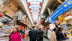 Kuromon Market in Osaka, Japan. Low angle track shot. Famous and attractive Japan food market with street food, quality produce, meats, prepared foods, and