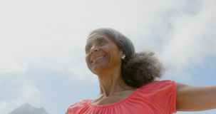 Low angle view of active senior African American woman stretching her arms in sunshine on the beach. She is smiling and looking away 4k stock footage
