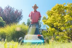 Active senior man smiling while using a grass cutting machine. Low-angle view of an active senior man smiling and looking at camera while using a grass cutting royalty free stock photo
