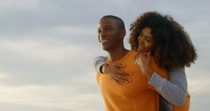 Low angle view of African american man giving piggyback ride to woman on the beach 4k. Low angle view of African american man giving piggyback ride to woman on stock video footage
