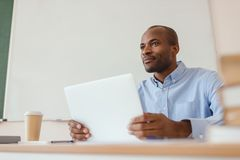 Low angle view of african american teacher sitting at desk with laptop and coffee. Cup Royalty Free Stock Photography